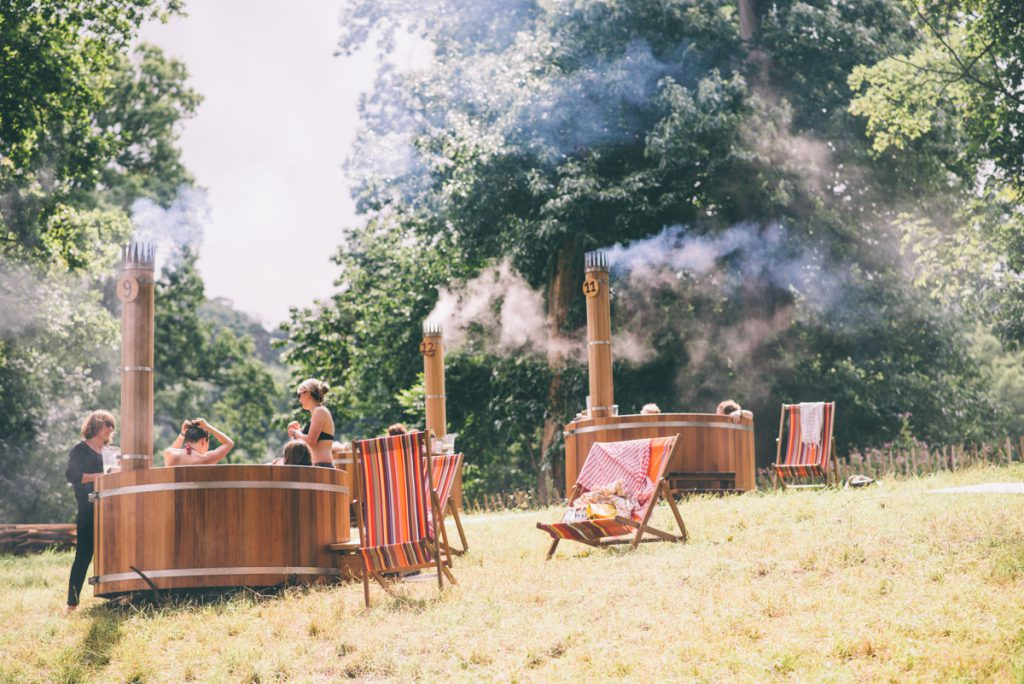 People in and around a couple of hot tubs in a field with a few deck chairs strewn around