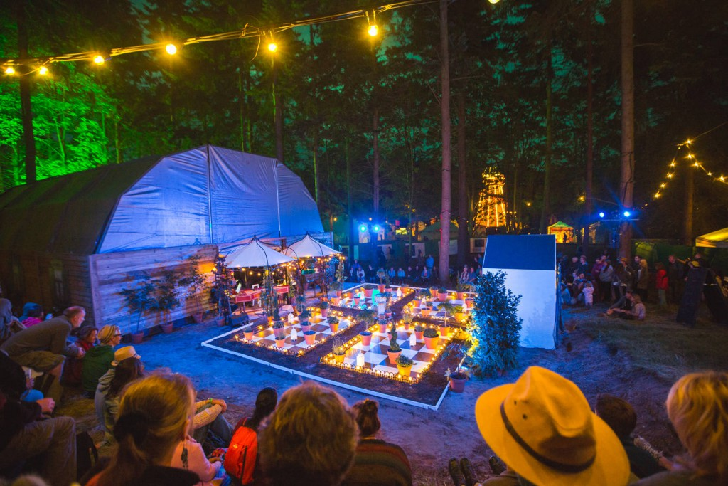 Crowd gathered around a lighted up performance in a forest