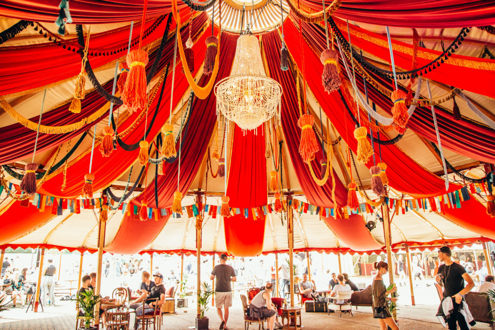 People seated as well as ambling through a red draped tent with a chandelier