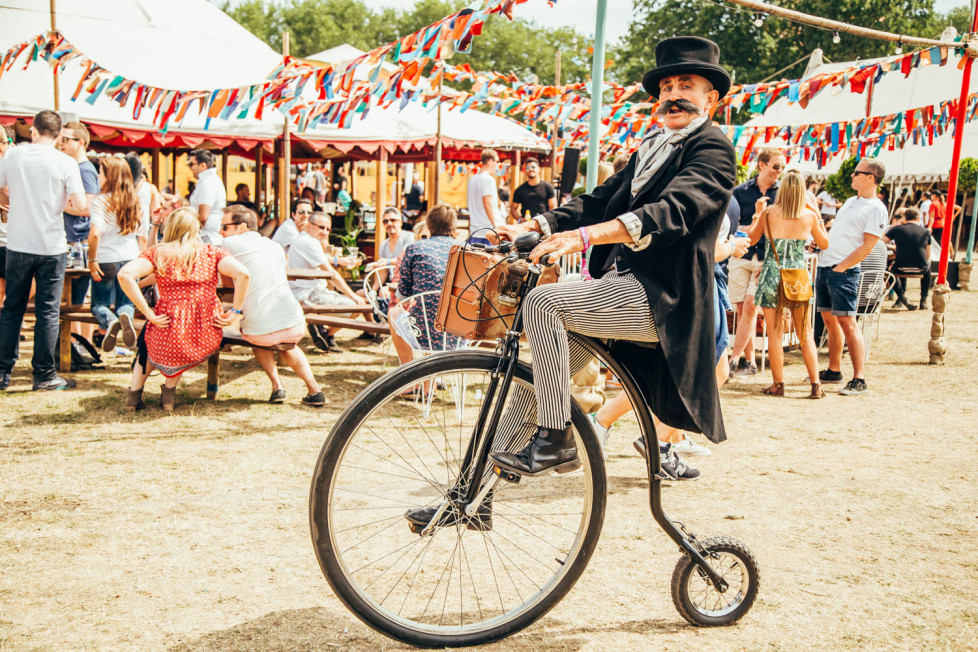 Man in a top hat and suit riding a penny farthing