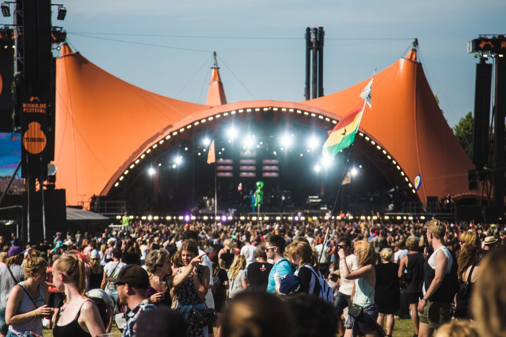 Orange tented stage with crowd in front of it