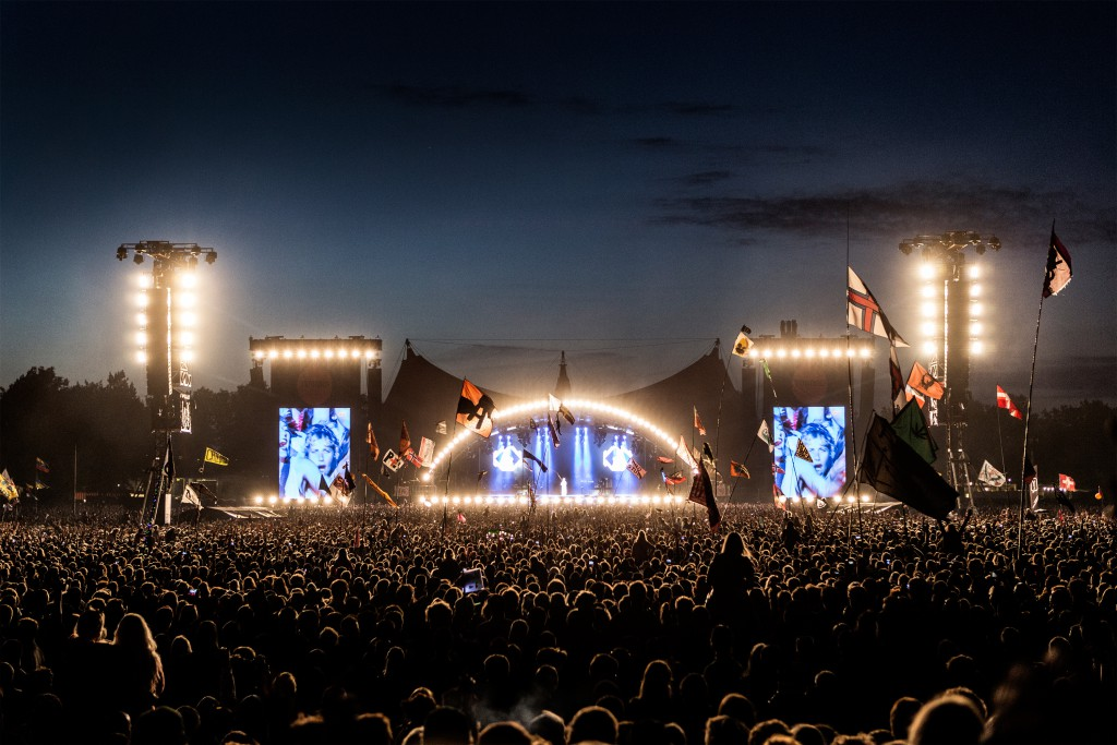 Night shot of the huge audience and lighted up stage in the background at Roskilde Festival