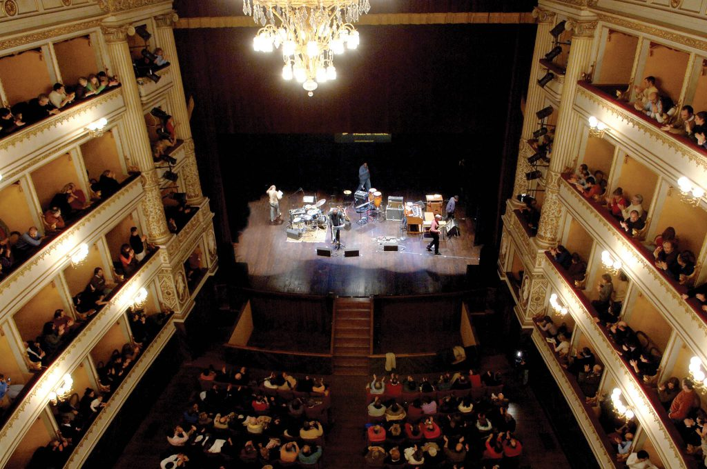 Overhead view of the audience in theatre balconies and ground floor watching a band perform on stage