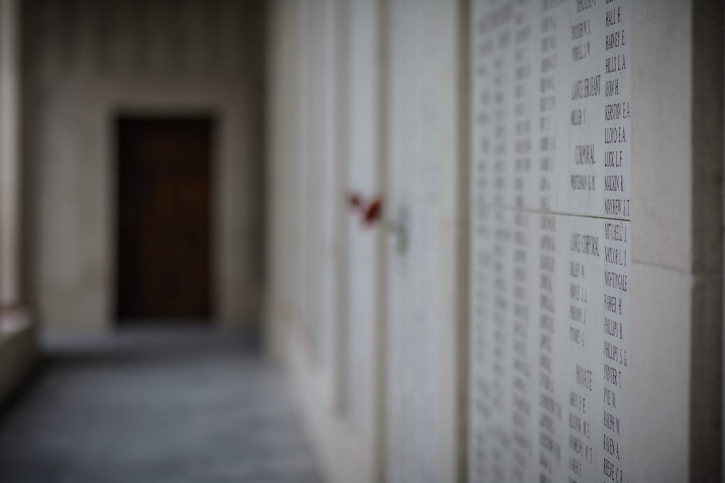 Wall with names of fallen soldiers and dates down a corridor