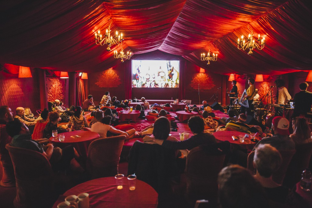 People seated at tables watching a movie in a plush red tent at the Wilderness Festival