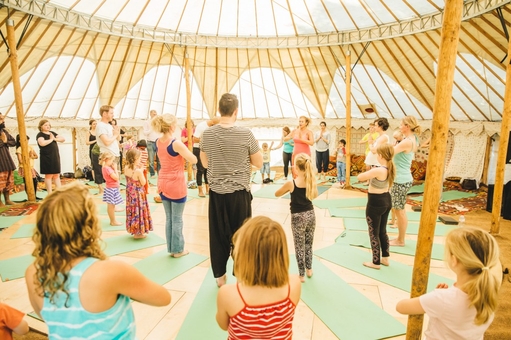 Adults and children practicing Acro yoga in a tent