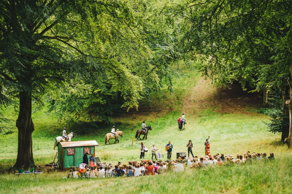 Band playing in the woods to an audience seated in the grass with four horse riders in the background