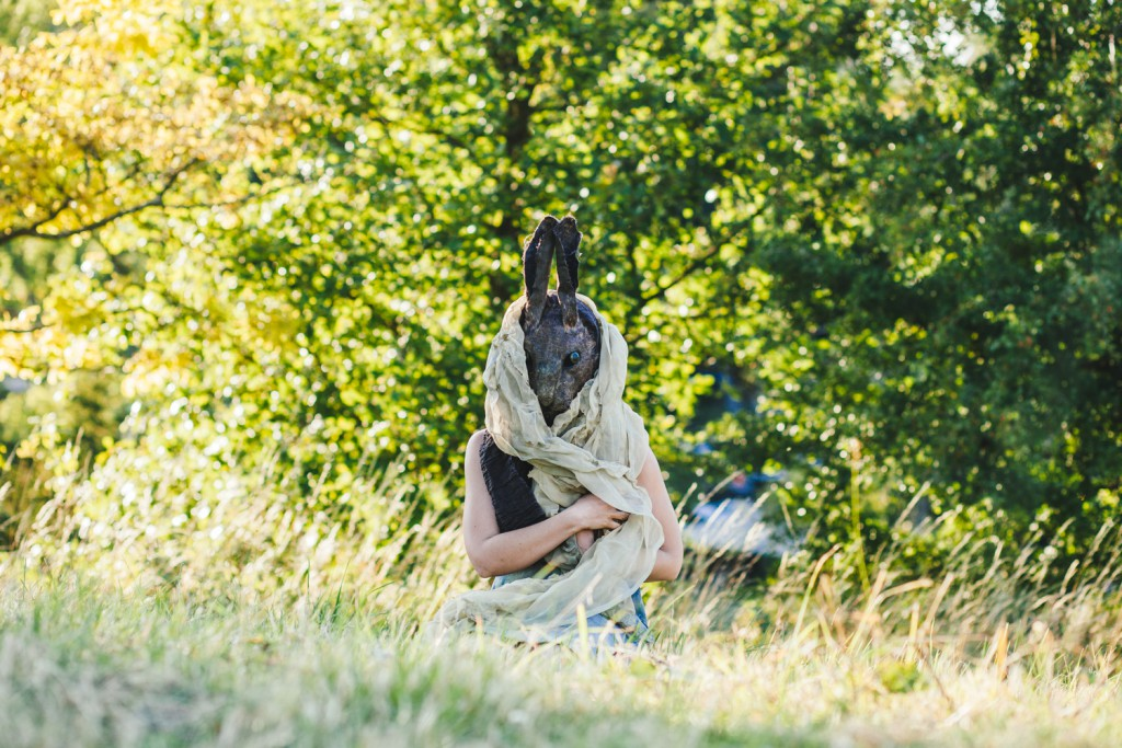 Woman in a donkey mask sitting on grass with a shawl wrapped around her head