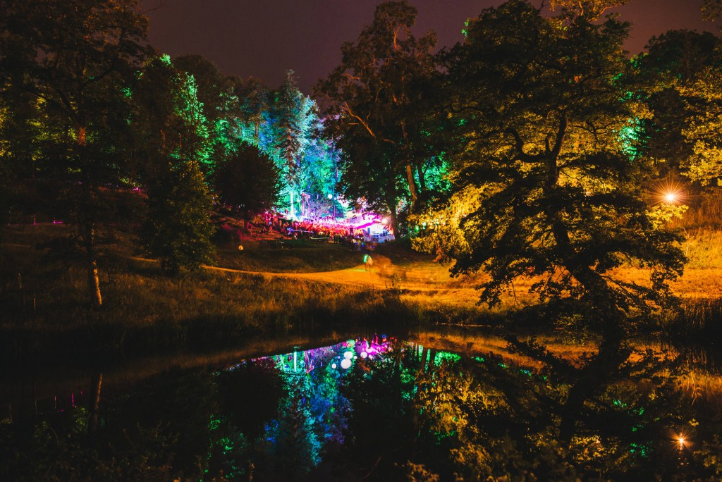 The Wilderness Festival glade lighted up at night