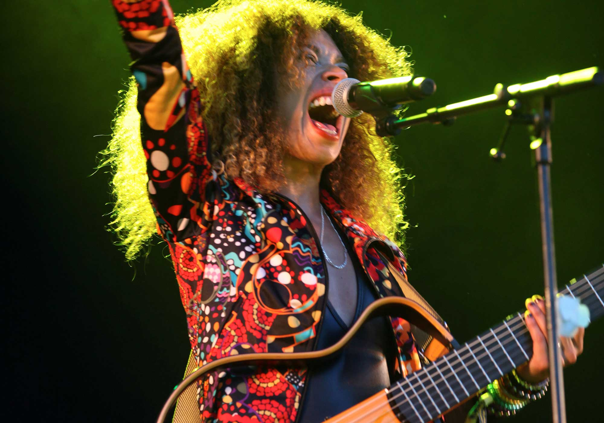A colourfully dressed woman guitarist screaming out a song with raised right arm, at, WOMAD, Taranaki