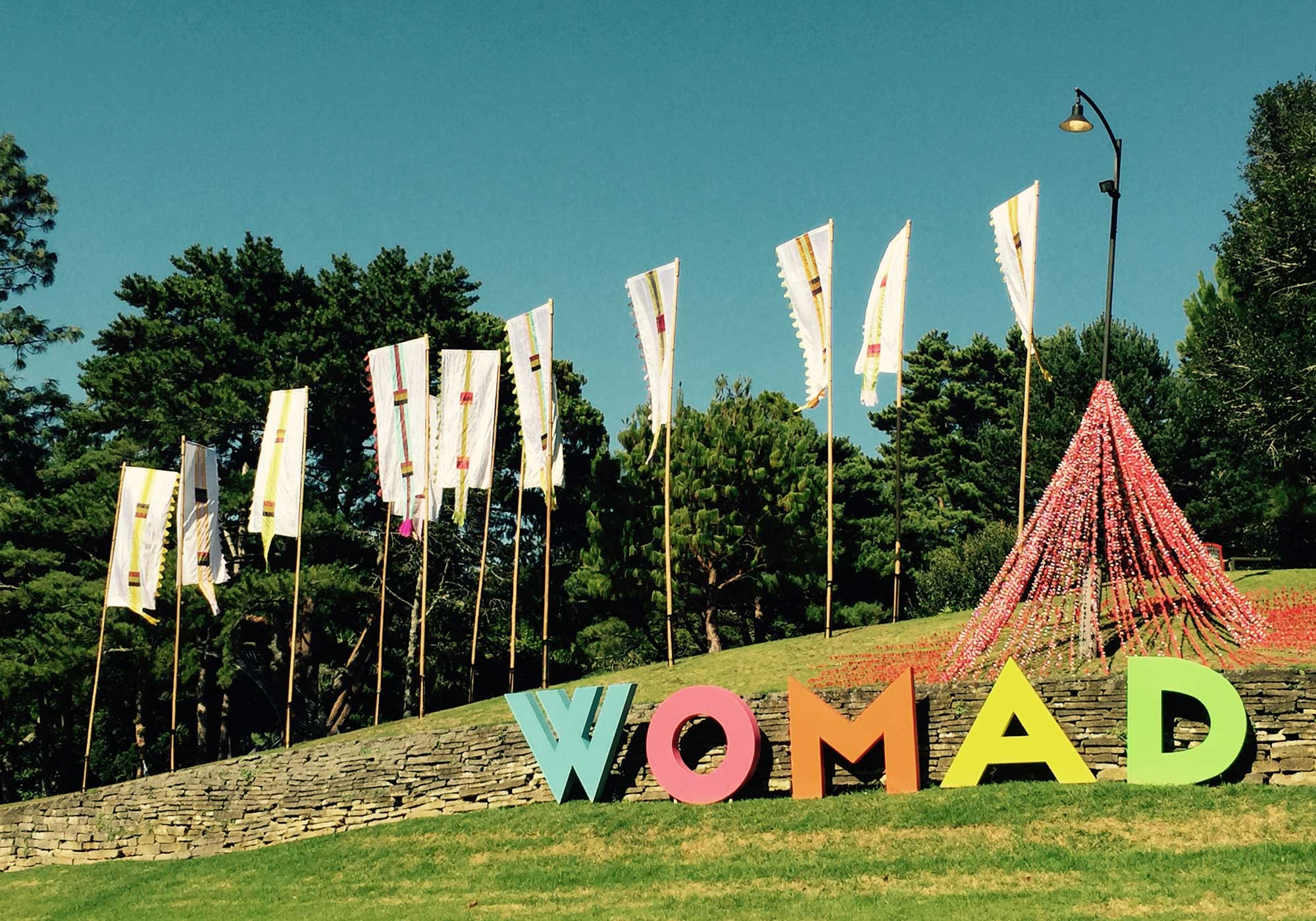The letters WOMAD set against a small ridge and flags fluttering behind them