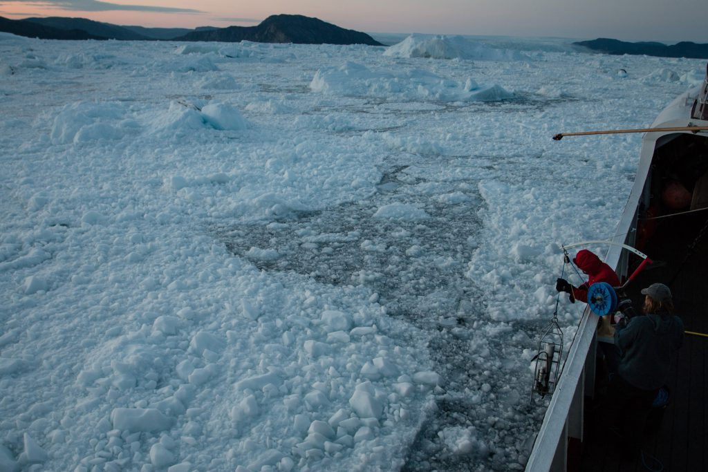 Researchers lowering a measuring device into the icy sea off west Greenland.