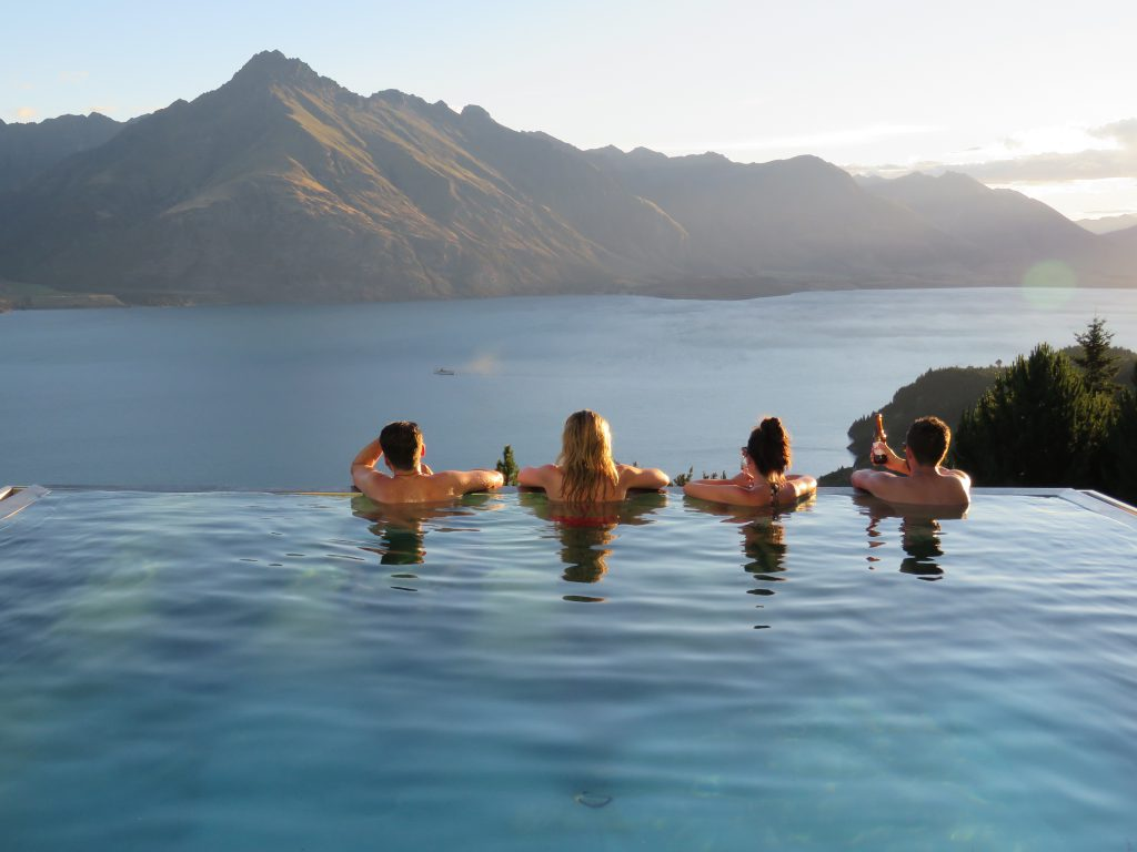 Group of four admiring the view over Lake Wakatipu from the end of Jagged Edge's infinity pool.