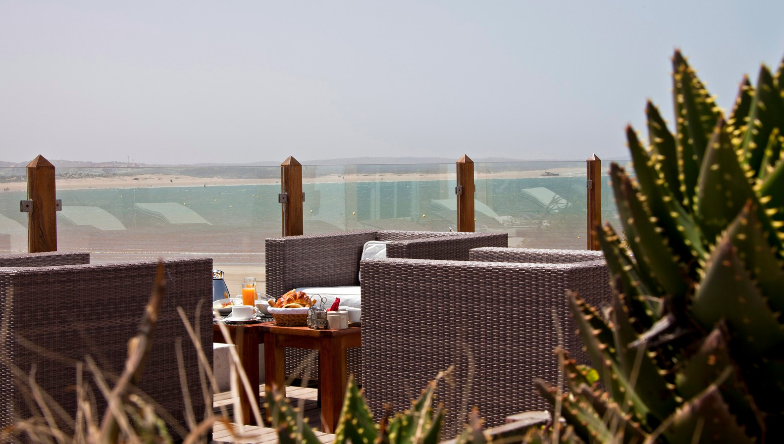 Breakfast meal placed on a low table between three outdoor armchairs overlooking the sea, Villa de L'Ô, Essaouira, Morocco
