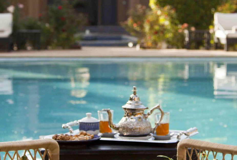 A breakfast tray served on a low table between two seats by the pool, Palais de L'Ô, Marrakech, Morocco
