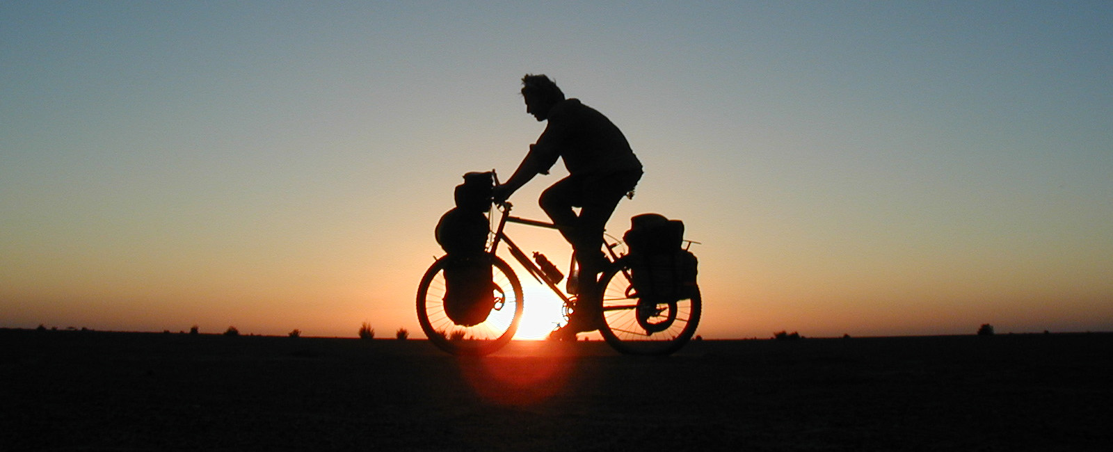Alastair Humphreys cycling with bags on his bicycle silhouetted against the setting sun in Sudan