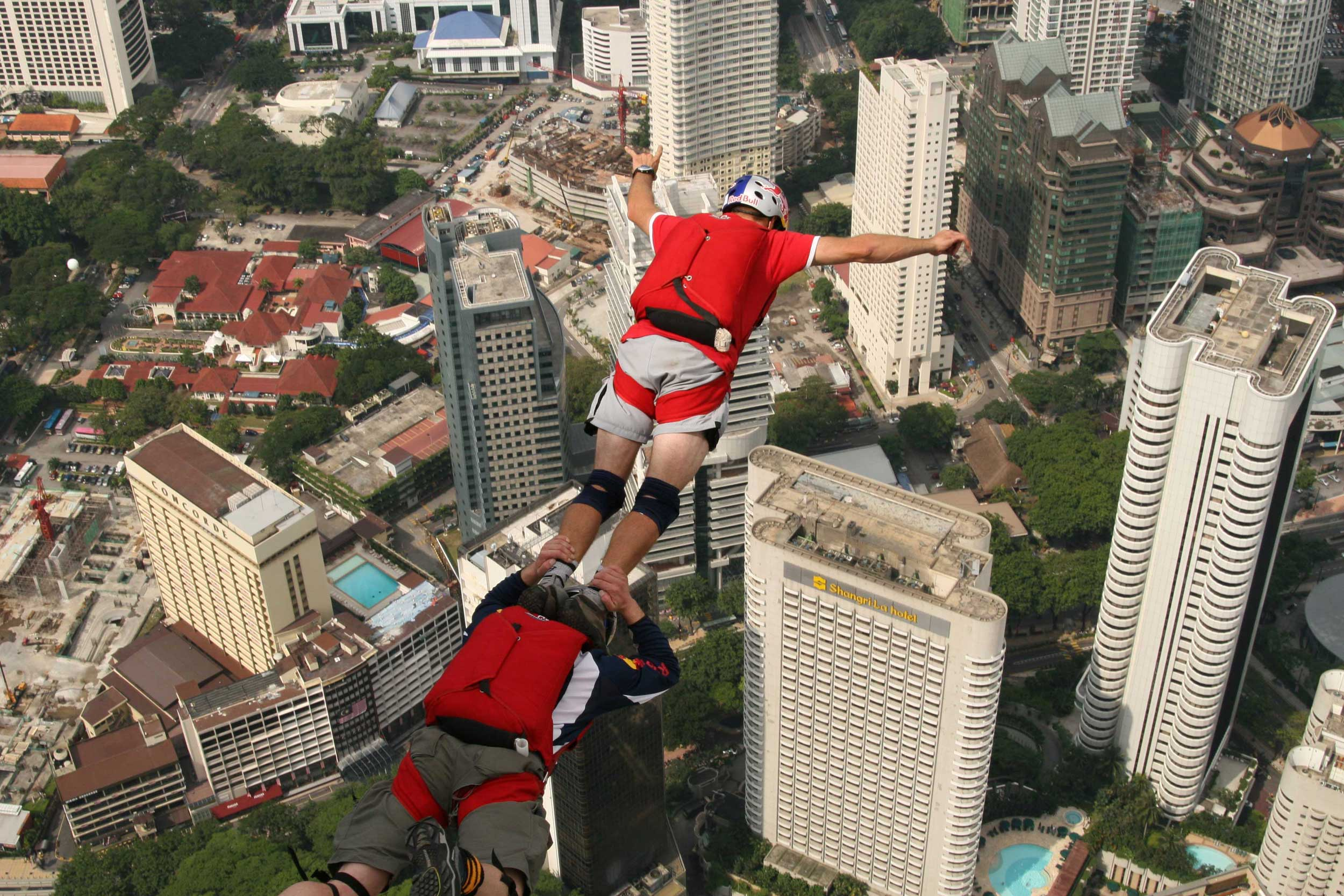 Man standing on anothers' shoulders and both jumping off a building down towards buildings below them in Kuala Lumpur
