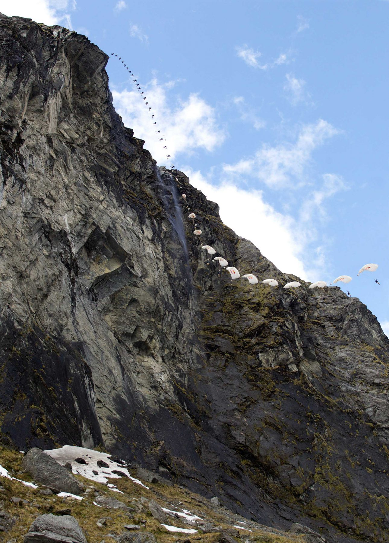 A time-lapse sequence of a base jumper coming down a craggy mountain rangein Wanaka, New Zealand