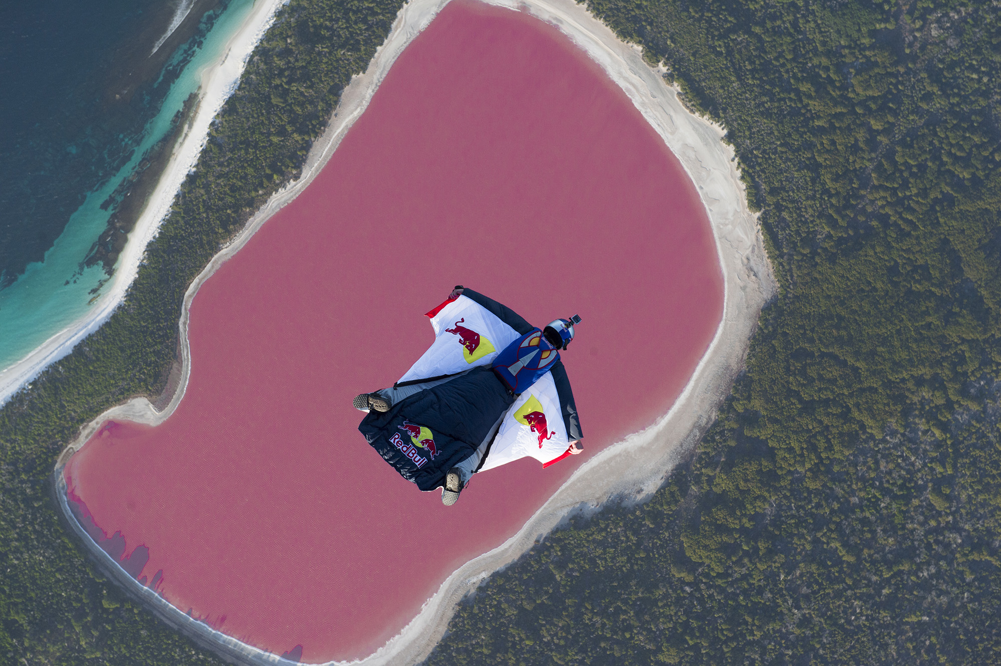 Chuck Berry spreadeagled in a wingsuit floating down to a very pink lake