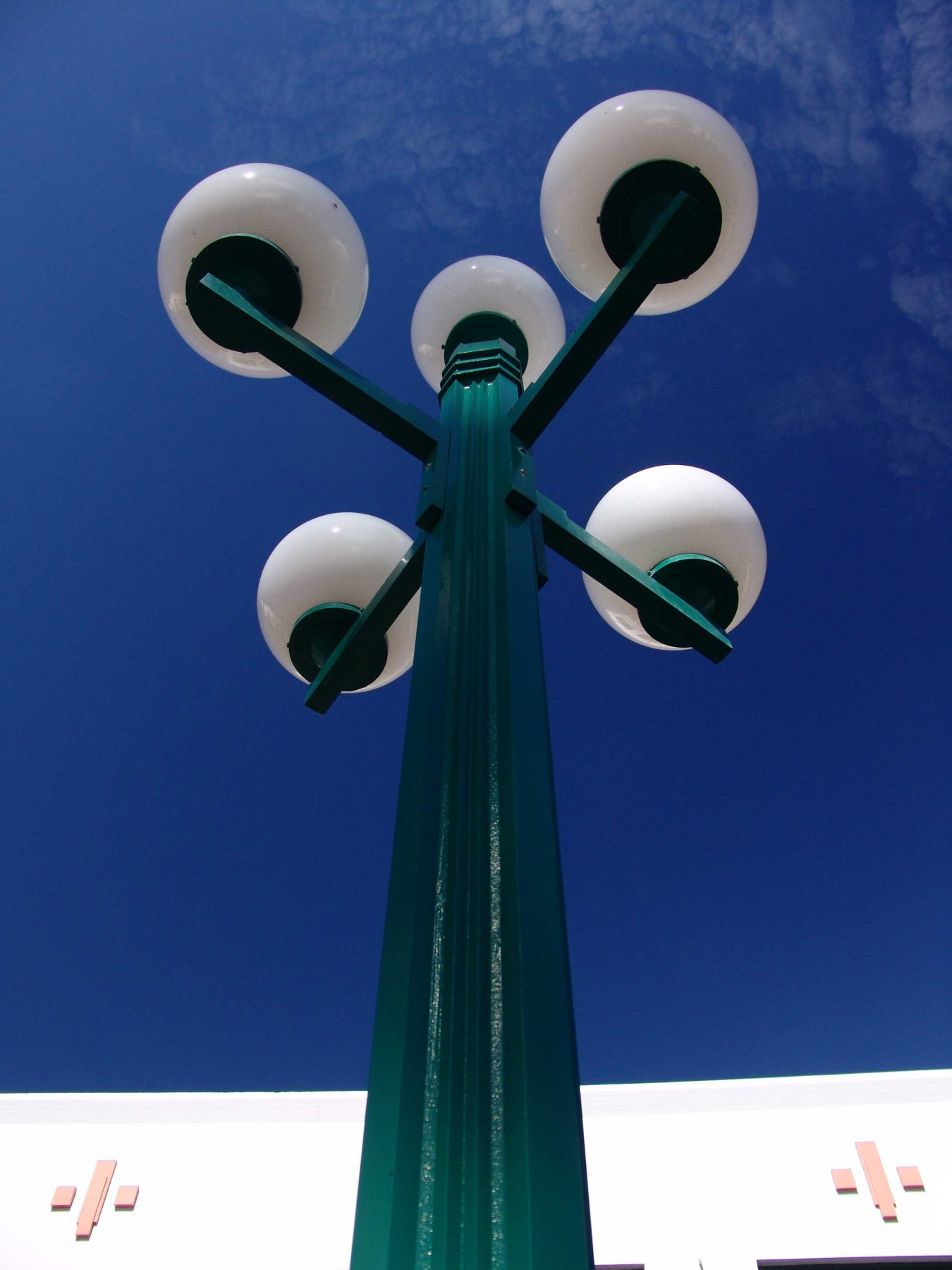 Looking up at a green streetlamp five white globe shades