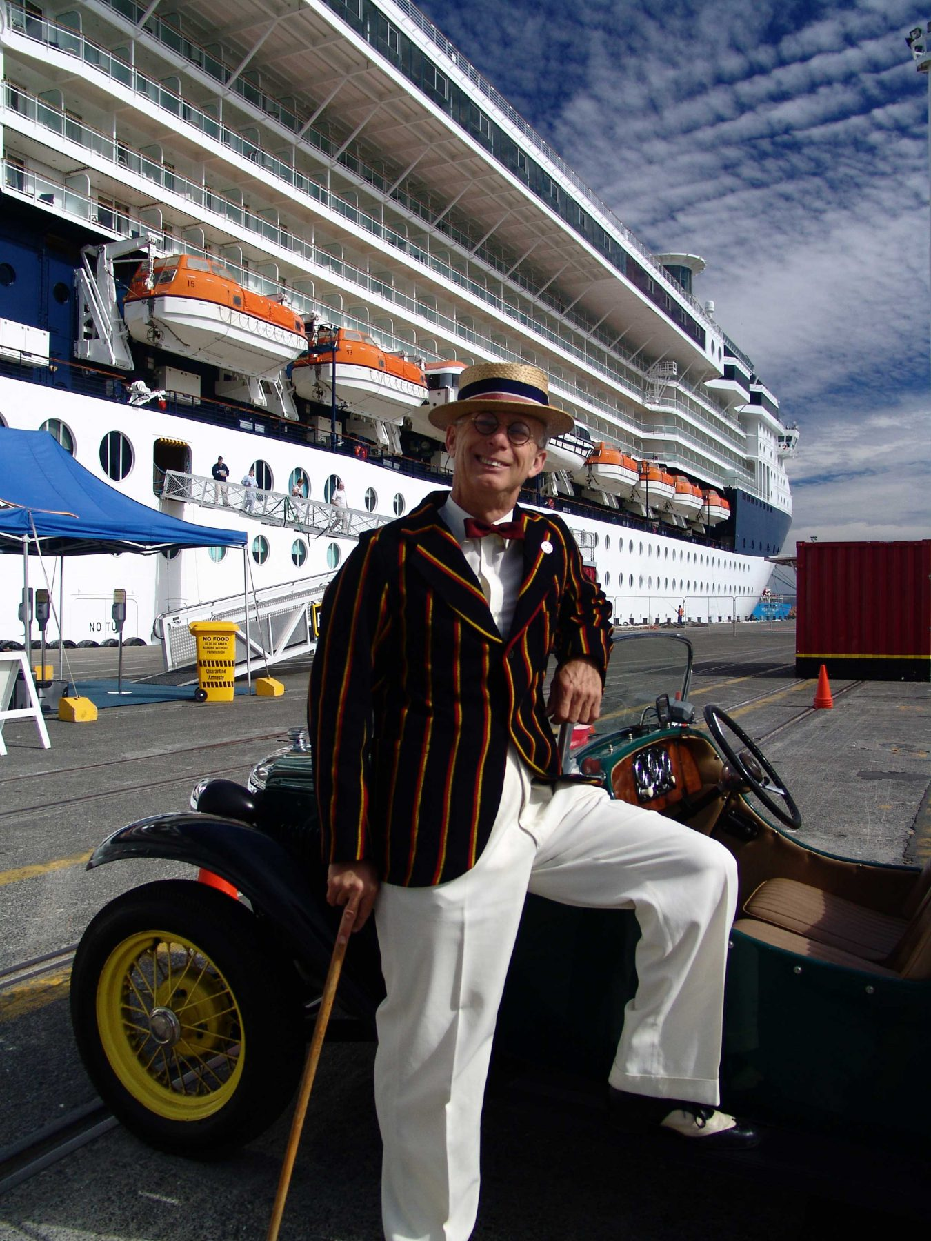 Man dressed in period costume by his car on the Napier docks with a cruise liner behind him