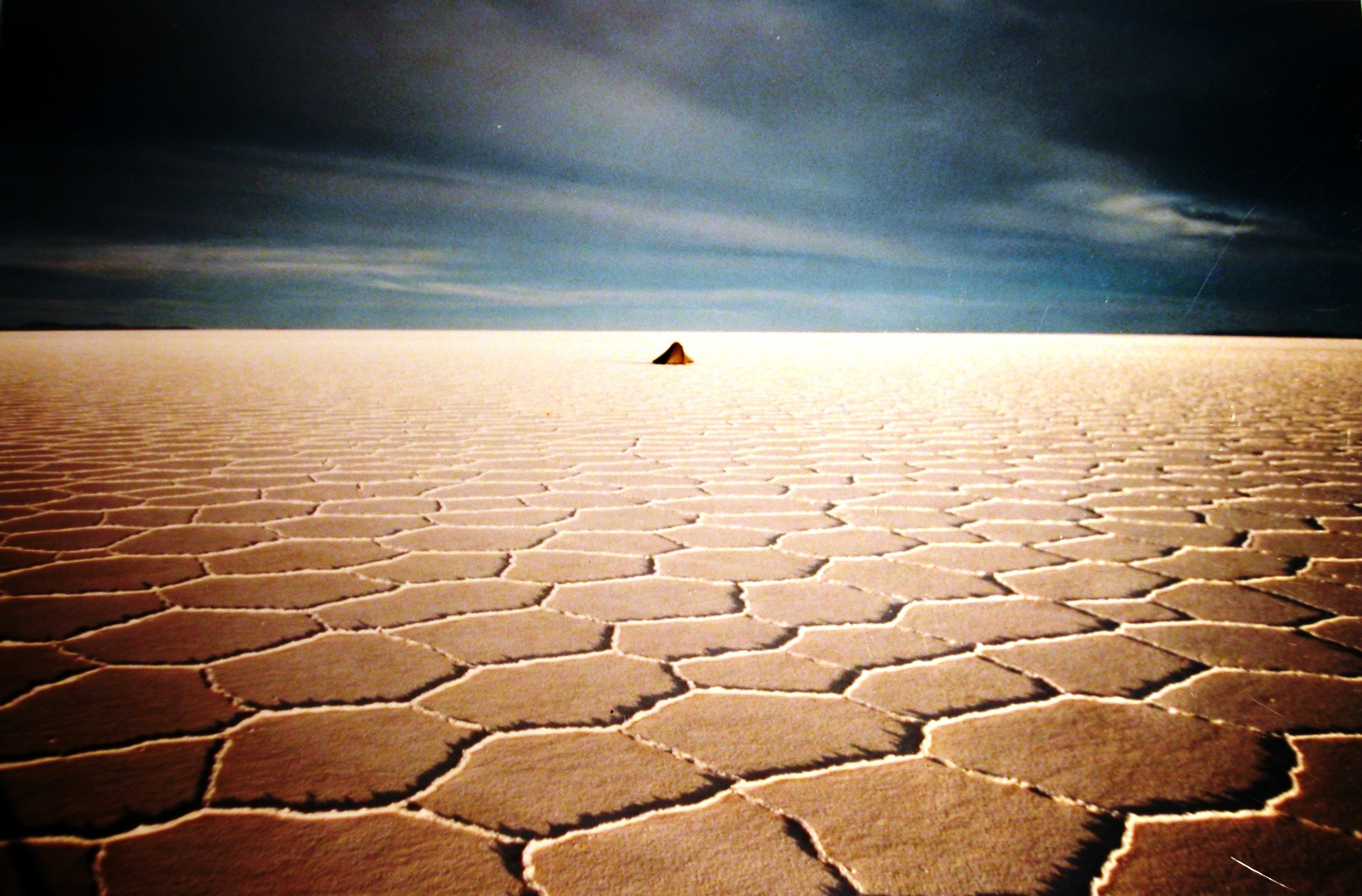 A minute tent in the distance on a barren, cracked desert floor in Bolivia