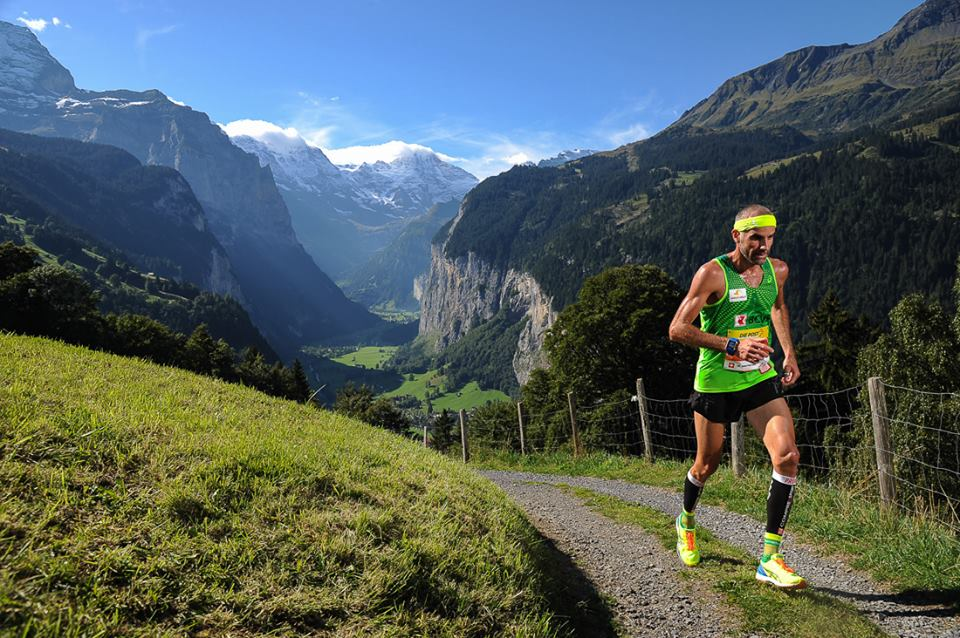 Man runningin the mountains in the Jungfrau marathon dressed in a green singlet with yellow shoes and headband