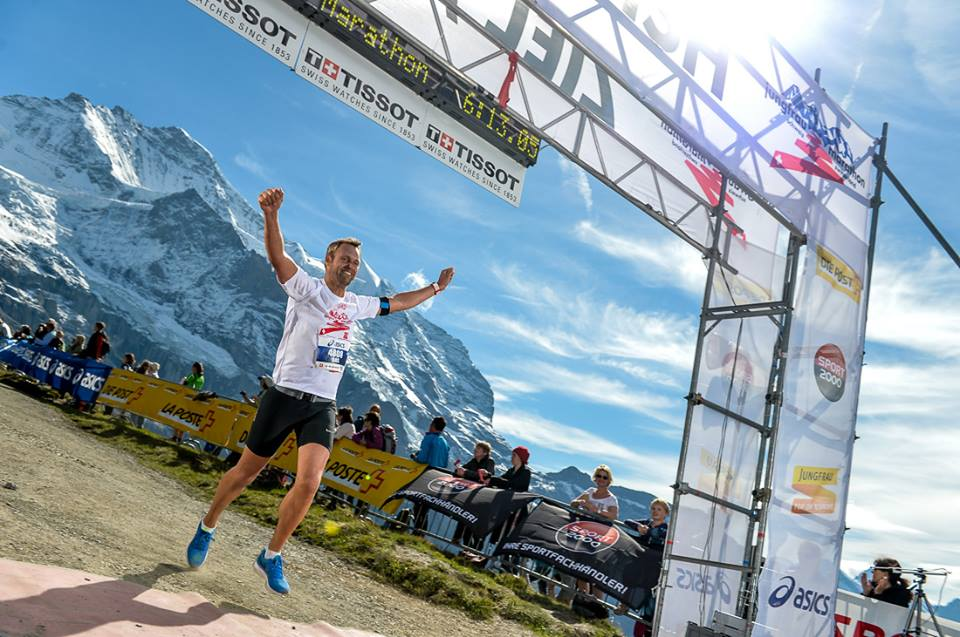 Runner in the Jungfrau marathon dressed in a white T-shirt crossing the finish line with raised arms and spectators on the sidelines, Jungfrau, Switzerland