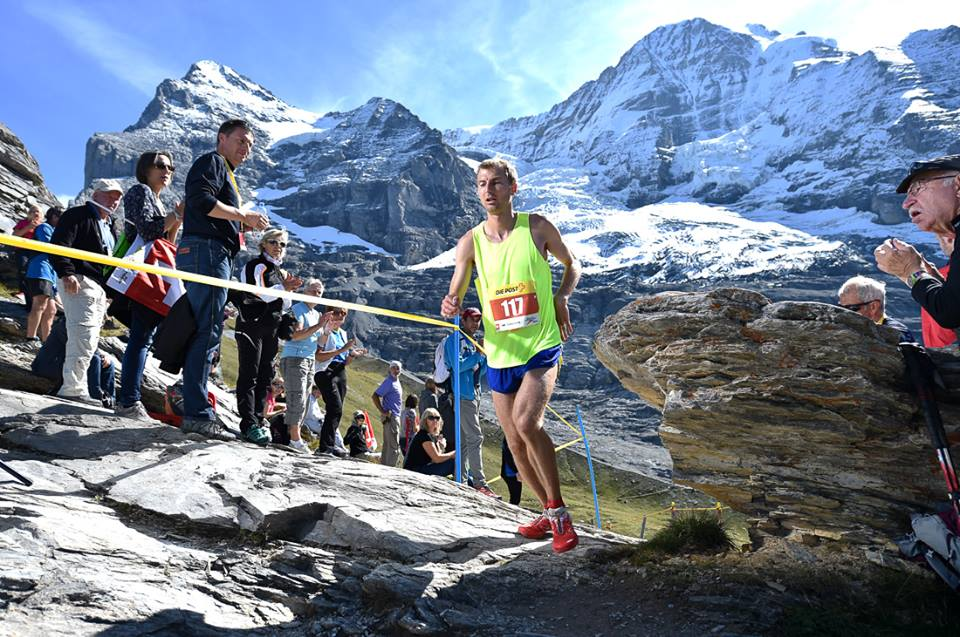 Runner dressed in a yellow singlet running past the crowd standing by a railing in the Jungfrau marathon in Switzerland