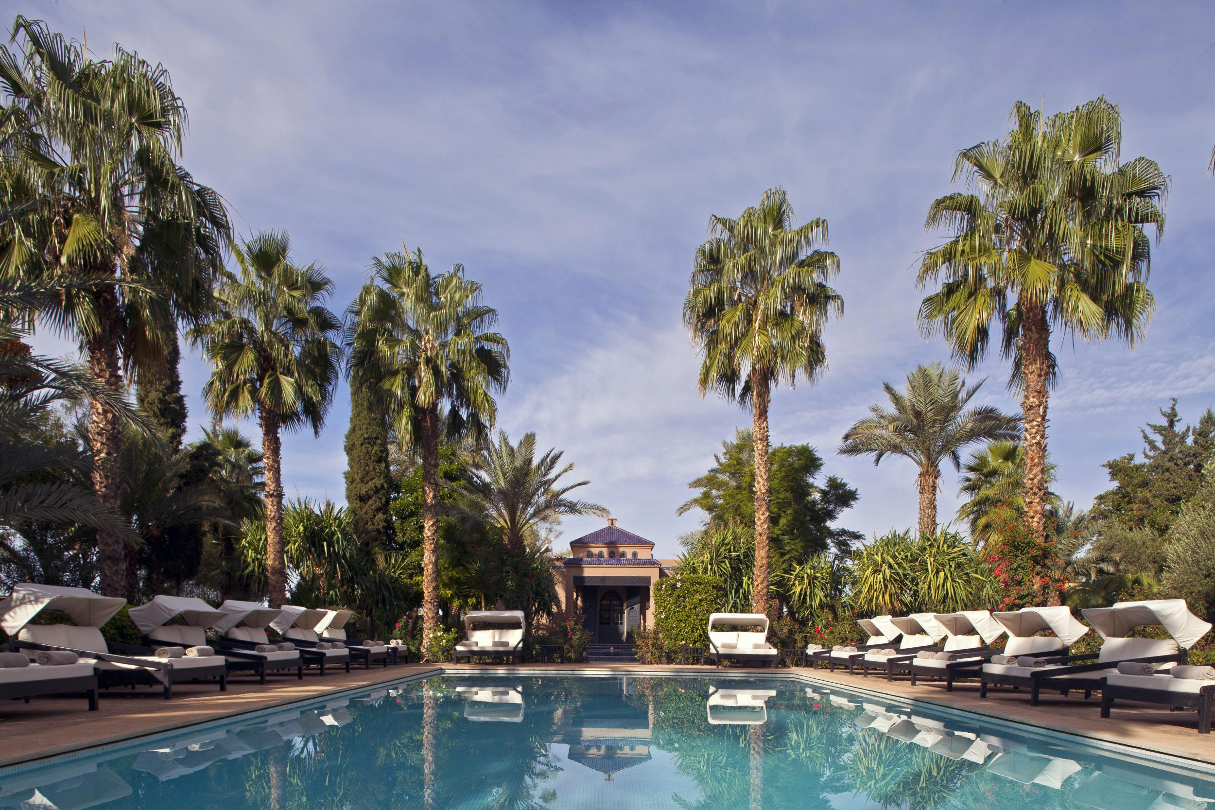 View of the swimming pool surrounded by double shaded loungers and palm trees, Palais de L'Ô, Marrakech