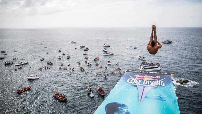 Red Bull Cliff Diving: Man curled up after launch off the Red Bull diving board with spectators in several boats in the sea below