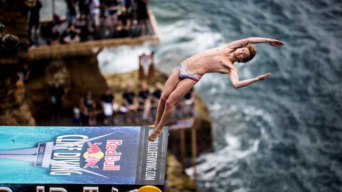Red Bull Cliff Diving: Close shot of man flipping backwards off the Red Bull diving board