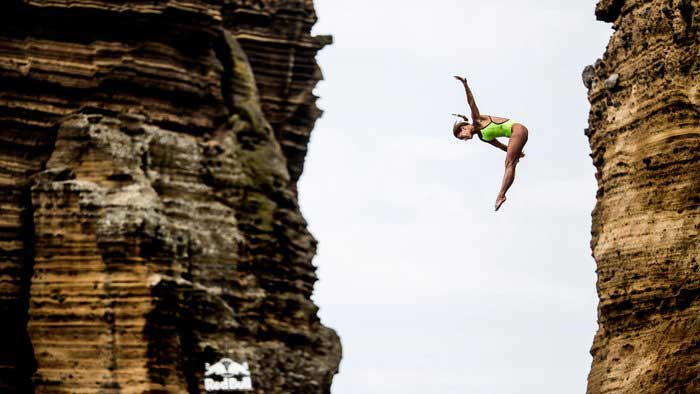 Red Bull Cliff Diving: Girl in green swimsuit in mid-dive and bent over mid-flip with one arm raised
