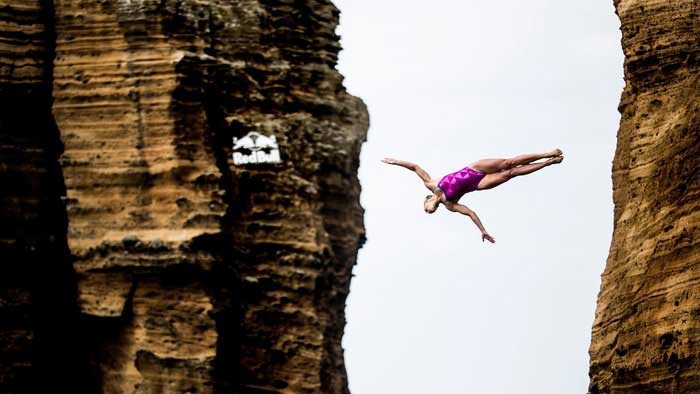 Red Bull Cliff Diving: Girl in pink swimsuit mid-dive between cliffs at the Red Bull Cliff Dive