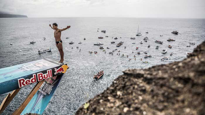 Red Bull Cliff Diving: Man poised on his toes at the edge of the Red Bull diving board with spectators in several boats on the sea beyond him