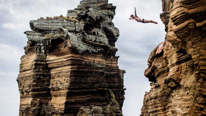 Red Bull Cliff Diving: Man with arms spread wide in mid-dive between striated cliffs