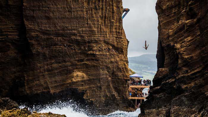 Red Bull Cliff Diving: Man diving vertically down between cliffswith spectators on ramps by the sea watching at the Red Bull Cliff Dive