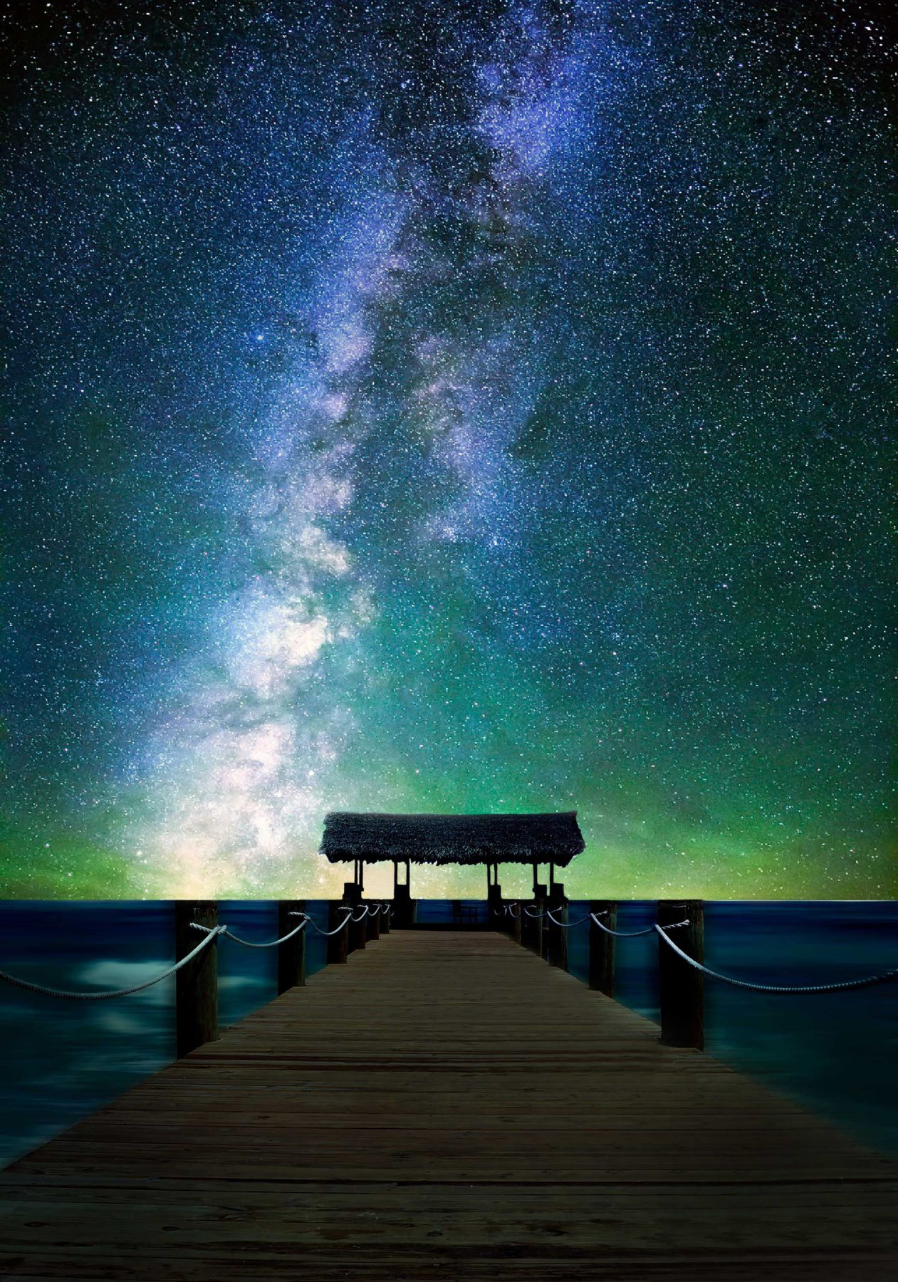 Wooden walkway leading to a thatched jetty under a very starry, blue and green streaked night sky, one of many romantic destinations in The Bahamas
