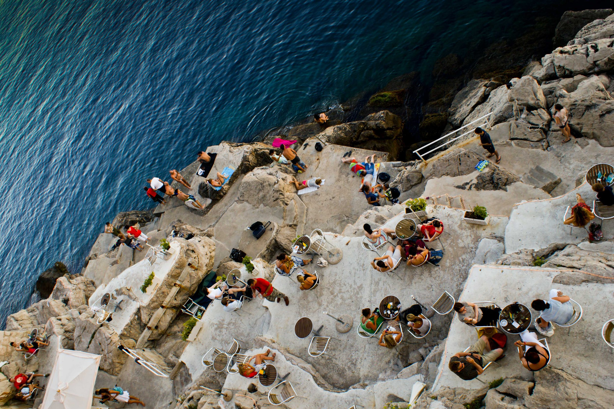 Aerial view of Buza Bar with groups seated at tables on the rocks, one of many romantic destinations in Croatia