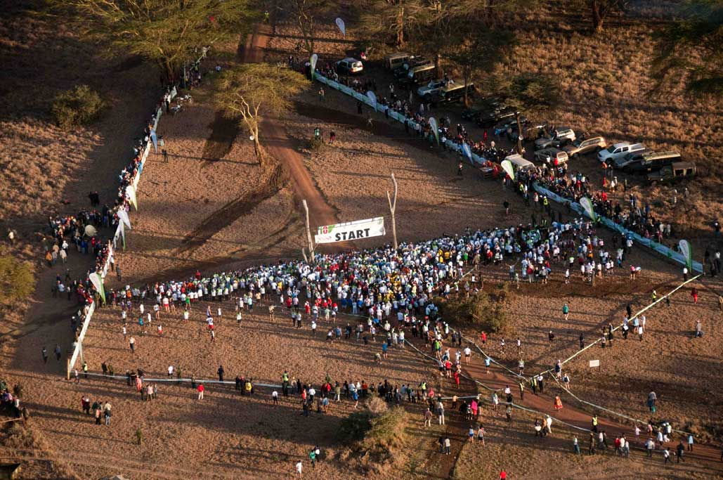 An aerial view of the many competitors lined up at the start line and spectators lined up by the fences on either side in Kenya in the Safaricom Marathon