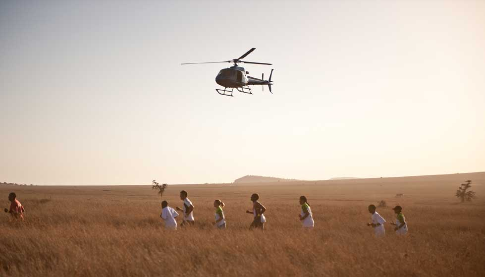 Helicopter hovering over people running through brown grass in Kenya in the Safaricom Marathon