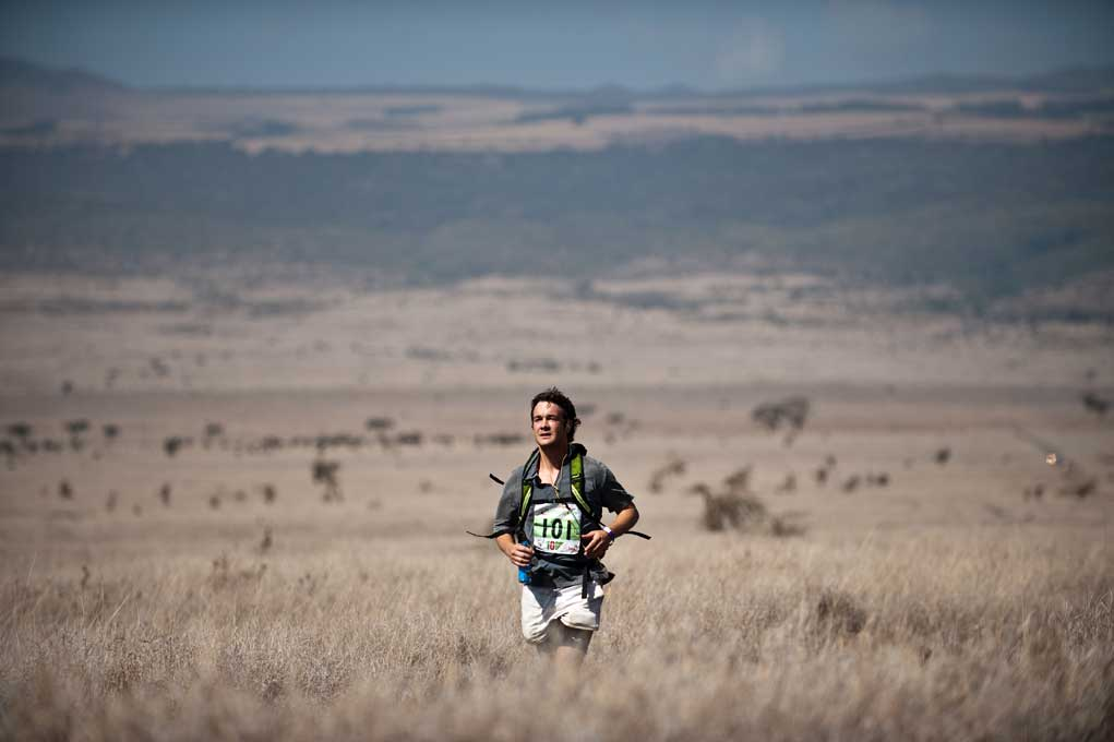 Solitary man running through thigh high grass and the empty plain stretching out behind him in the Safaricom Marathon