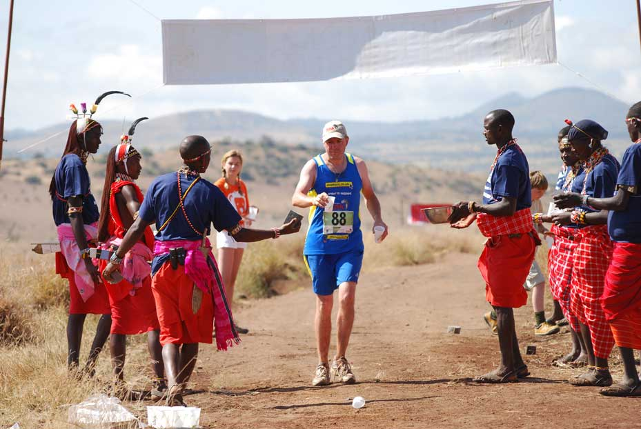 A runner grabbing refreshments at a rest stop from a group of Africans in local dress in Kenya during the Safaricom Marathon