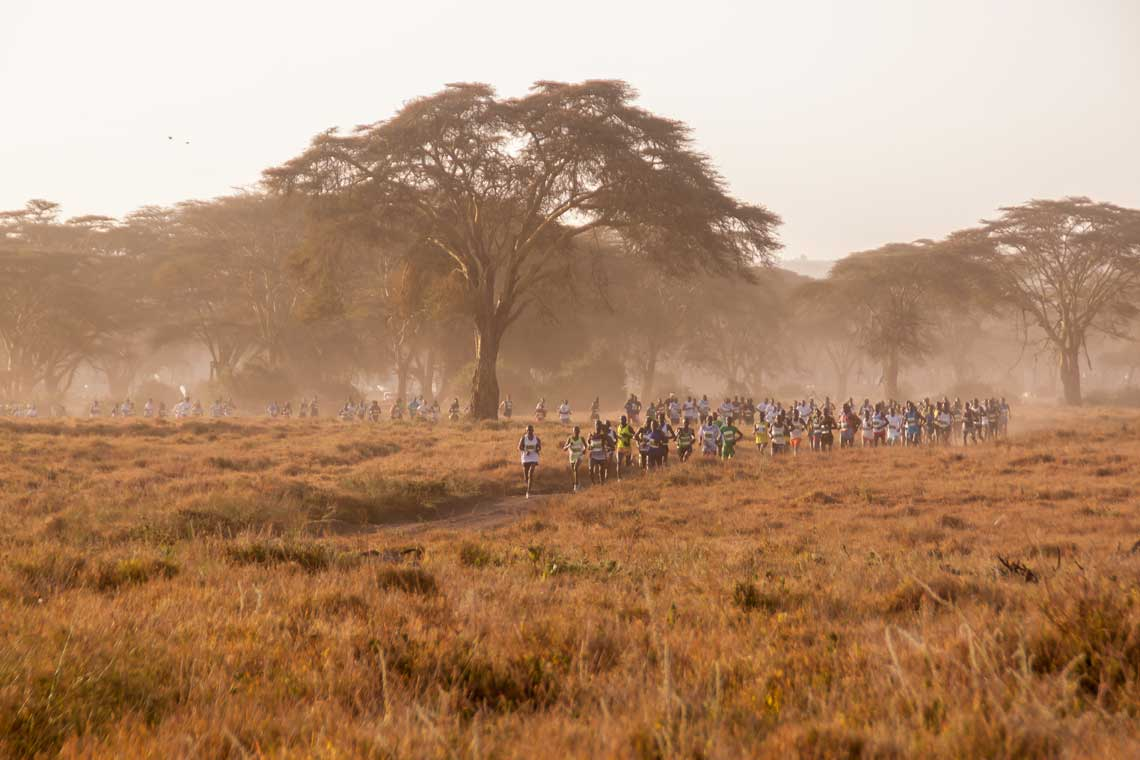 A long line of runners on a dusty track weaving through trees on the plain in Kenya in the Safaricom Marathon
