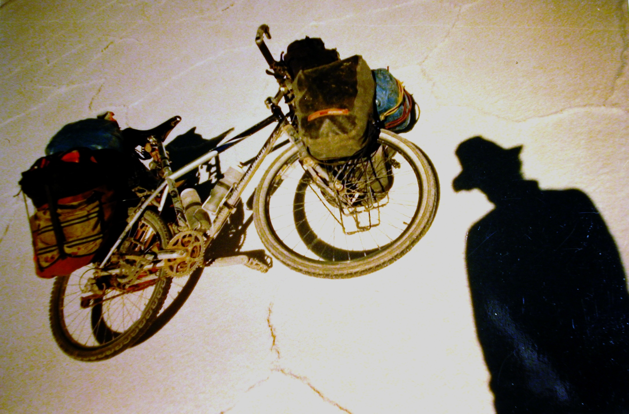 A man's shadow on the ground by a bicycle with bags strapped on the front and back