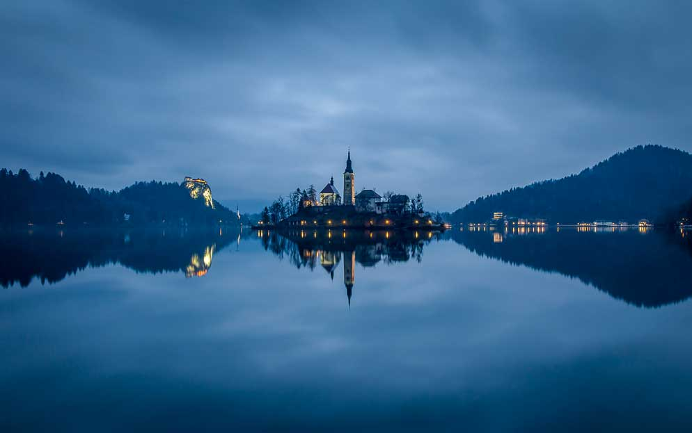 A lit up church on an island with lighted up buildings on either side of the banks of Lake Bled around it, Slovenia (Slovenia Explorer)