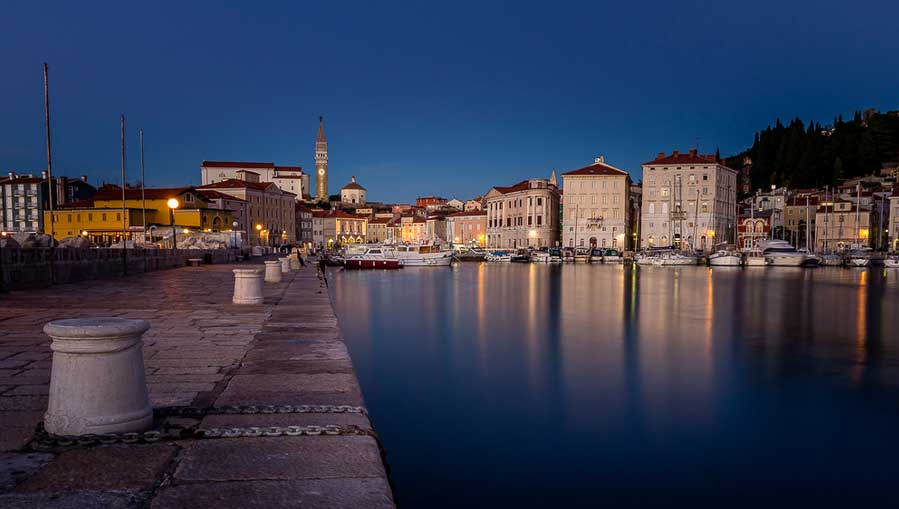 Stone walkway and bollards leading to mediaeval town buildings and berthed boats at sunset, Piran, Slovenia