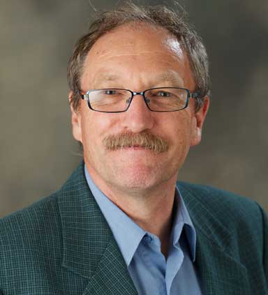 Close-up headshot of a smiling bespectacled and mustachioed man, Stephen Sparks as he discusses volcanic activity