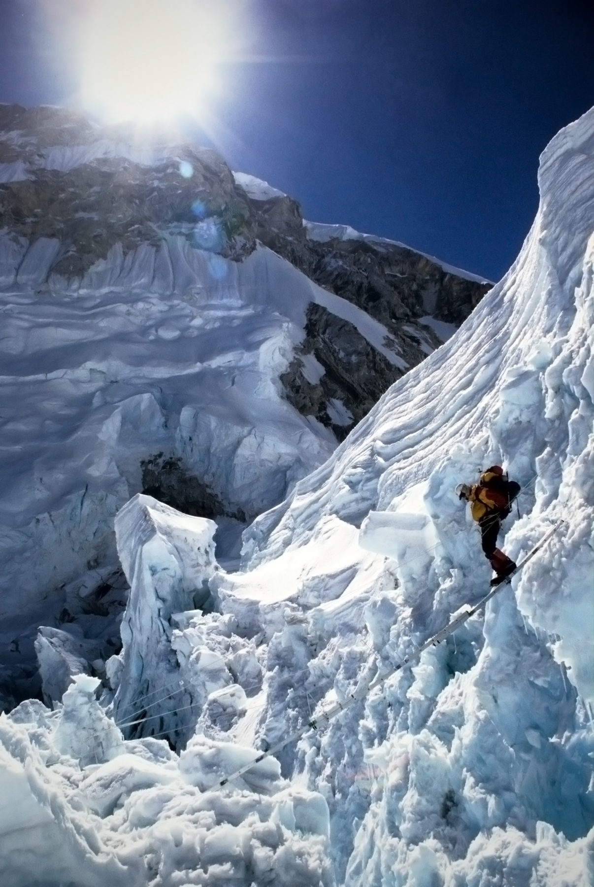 Mountaineer walking on a pole across a crevasse at a very snowy and icy Khumbu Icefall