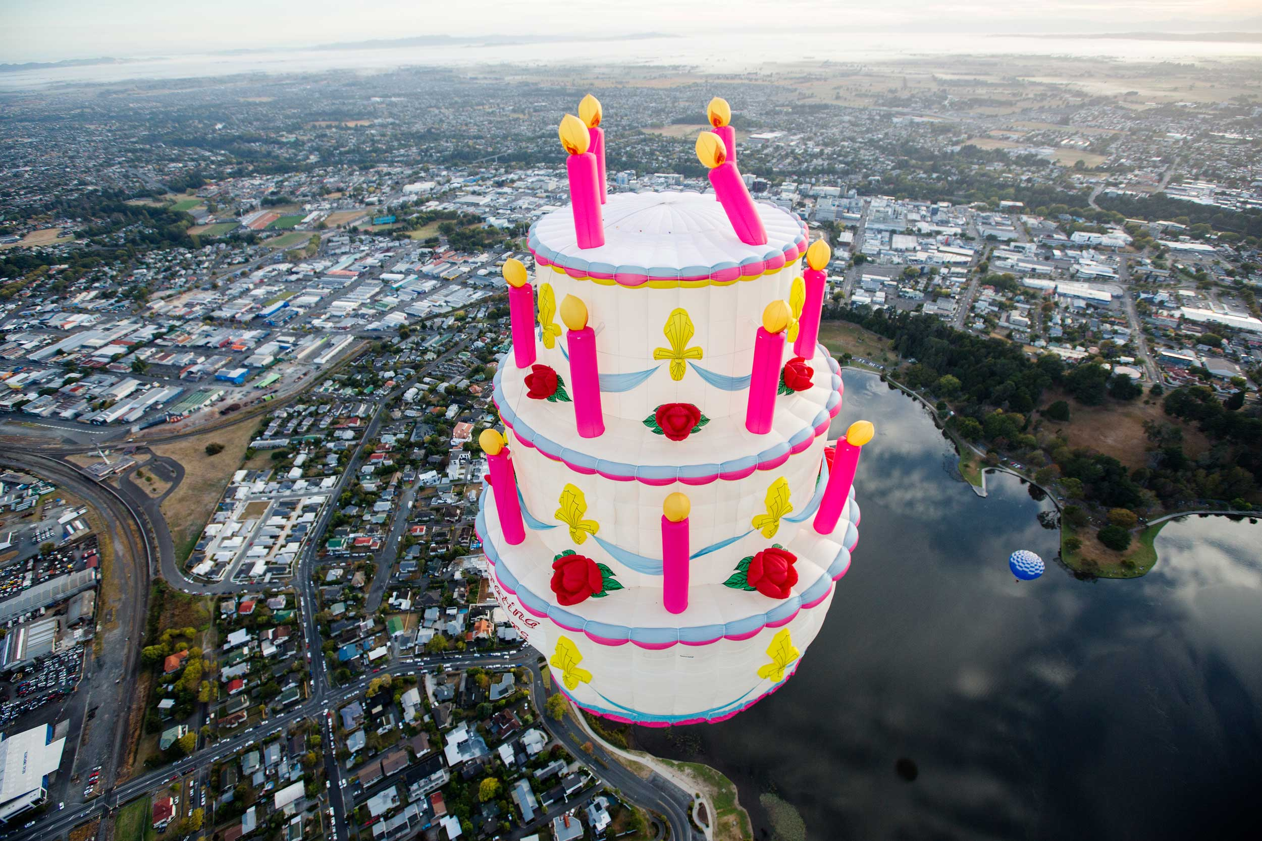 A very large and extravagant three tiered cake with candles balloon floating over Hamilton town at balloons Over Waikato festival, New Zealand